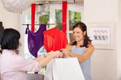 Saleswoman giving shopping bags to customer Stock Photos