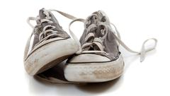 A pair of worn out gray sneakers on a white background Stock Photos