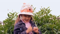 The little girl in panamanian, a hat laughs, spins Stock Footage