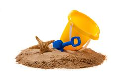 a yellow pail and blue shovel on the beach with a starfish - stock photo
