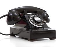 a retro black rotary phone on a white background - stock photo