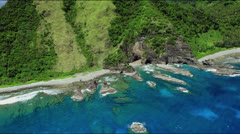 Flight along rocky outcrop with rain forest in the background Stock Footage