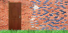 door on old brick wall with verdant grass & bright sky - stock photo