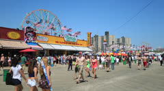 Coney Island boardwalk amusement park people walking Stock Footage