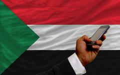 Cell phone in front  national flag of sudan Stock Photos