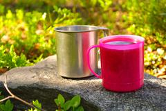 Two touristic cups metal and pink plastic with tea on stone in forest picnic  Stock Photos