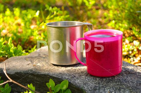 Stock photo of two touristic cups metal and pink plastic with tea on stone in forest picnic