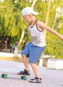 boy child training skateboard outdoor summer sport with nature on background - stock photo