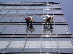 A man cleaning windows on a high rise building Stock Photos