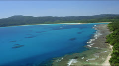 Aerial over waves rushing towards coral reef drop off and mangrove forest Stock Footage