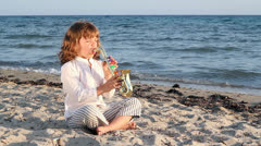 Little girl play saxophone on beach Stock Footage