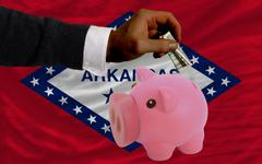 dollar into piggy rich bank and  flag of american state of arkansas - stock photo
