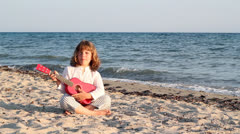 Little girl sing and play guitar on beach Stock Footage