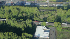 Aerial View of Freight Train Moving Through Industrial Area - stock footage