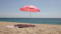 Umbrella and mat on a beach Stock Footage