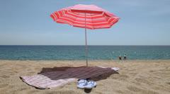 Mat and flip flops under a beach umbrella Stock Footage