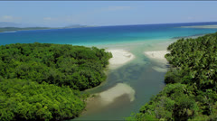 Flight around a river mouth flowing into the ocean with mangroves - stock footage