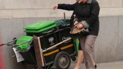 Woman puts rubbish in hand cart city of london refuse collection, england Stock Footage