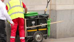 Man in high visibility jacket pushes hand cart refuse collection, england Stock Footage