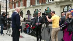 Tv crew interviewing police officer outside new scotland yard, London Stock Footage