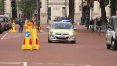 Emergency police car with siren and lights flashing approaches, london Stock Footage