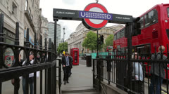 Red london bus passes underground station, england Stock Footage