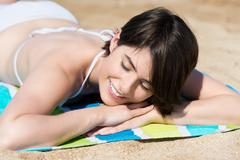 woman relaxing sunbathing on the beach - stock photo