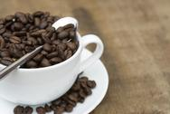 Cup of coffee and beans on wooden background Stock Photos