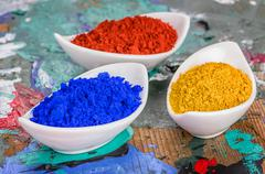 vibrant color pigments in porcelain bowls on a wooden palette - stock photo