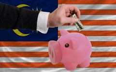 dollar into piggy rich bank and  national flag of malaysia - stock photo