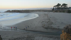 Visitors walk along the beach at sunset, time lapse - stock footage
