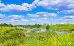 cloudy landscape with pond - stock photo