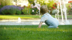 HD1080p25 Young baby (10 months old) exploring the meadow Stock Footage