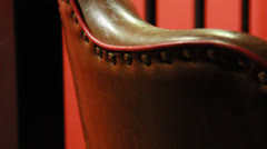 Leather chair, upholstery tacks, red background Stock Footage