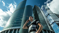The man stands and talk by phone near Moscow sky-scrapers Stock Footage