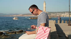 Man doing online shopping on tablet by the sea HD - stock footage
