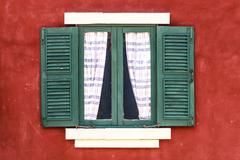 Old green window with curtain on red wall - stock photo