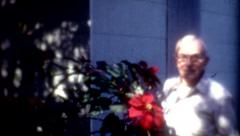 Elderly man smells red flower vintage fashion old film footage Stock Footage