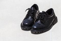 Old black shoes on footpath background Stock Photos