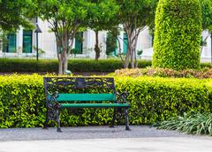 Green bench in the park with white building background - stock photo