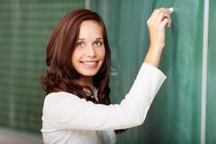smiling teacher writing on a blackboard - stock photo