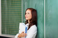 optimistic female student smiling and thinking - stock photo