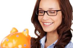 Stock Photo of smiling woman holding her piggy bank