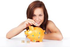 Woman putting coins in her piggy bank Stock Photos