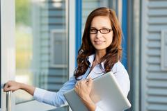 Woman carrying a laptop opening a door Stock Photos