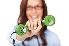 Woman holding out a telephone handset Stock Photos