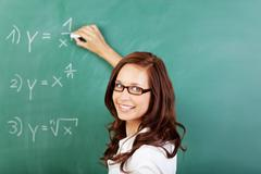 teacher writing mathematical equations - stock photo