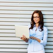 Woman standing and checking mails on laptop Stock Photos