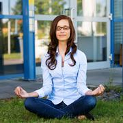 young woman sitting meditating - stock photo