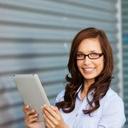 woman smiling and working on the ipad - stock photo